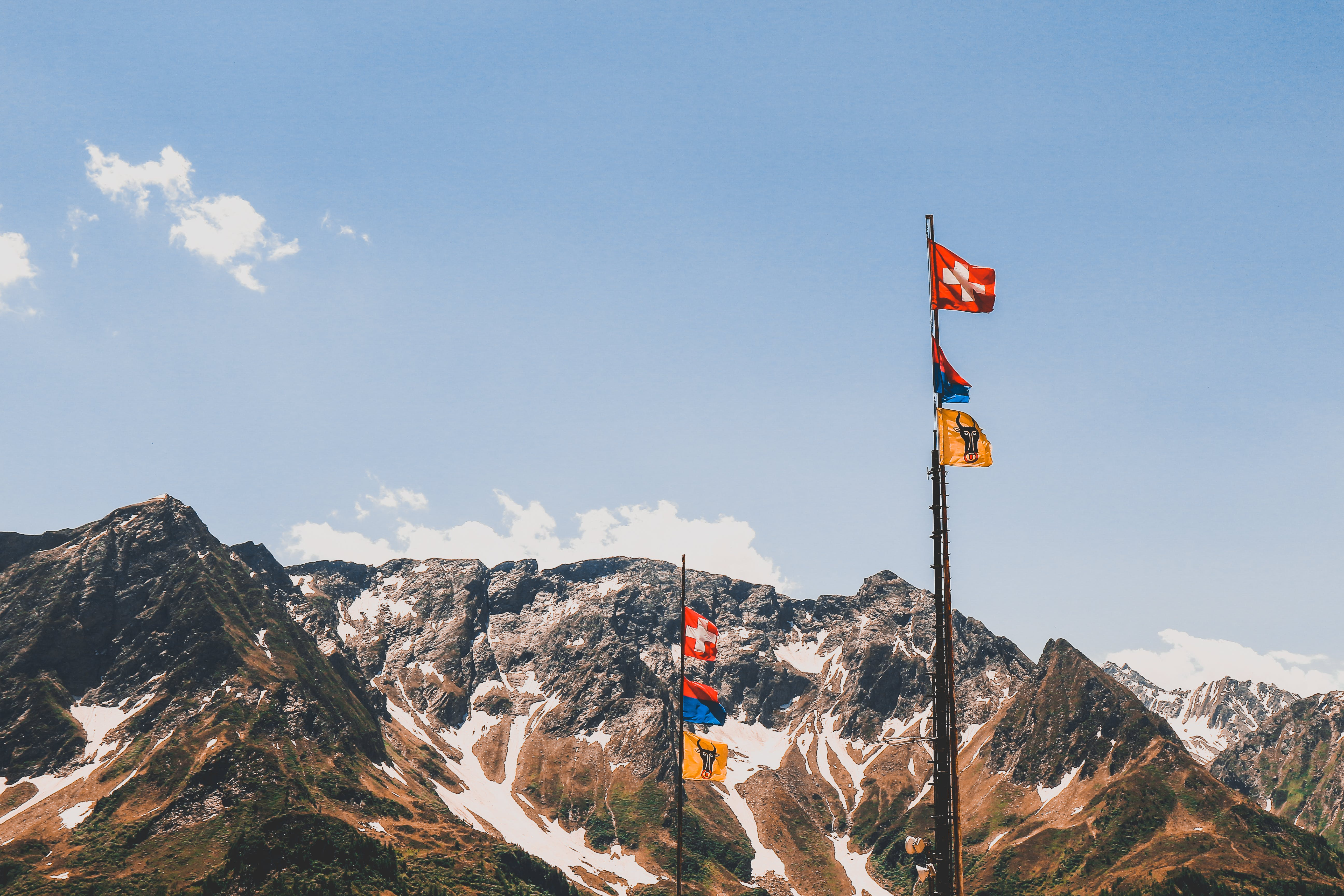 Photography Of Mountain Summit With Flags