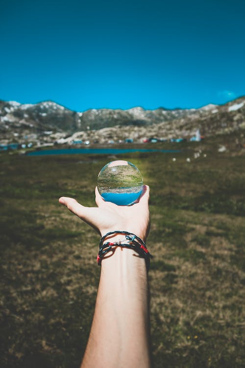 Person Holding Clear Globe Ball