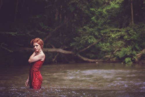 Woman in Red String Spaghetti Strap Dress on Body of Water Near Forest