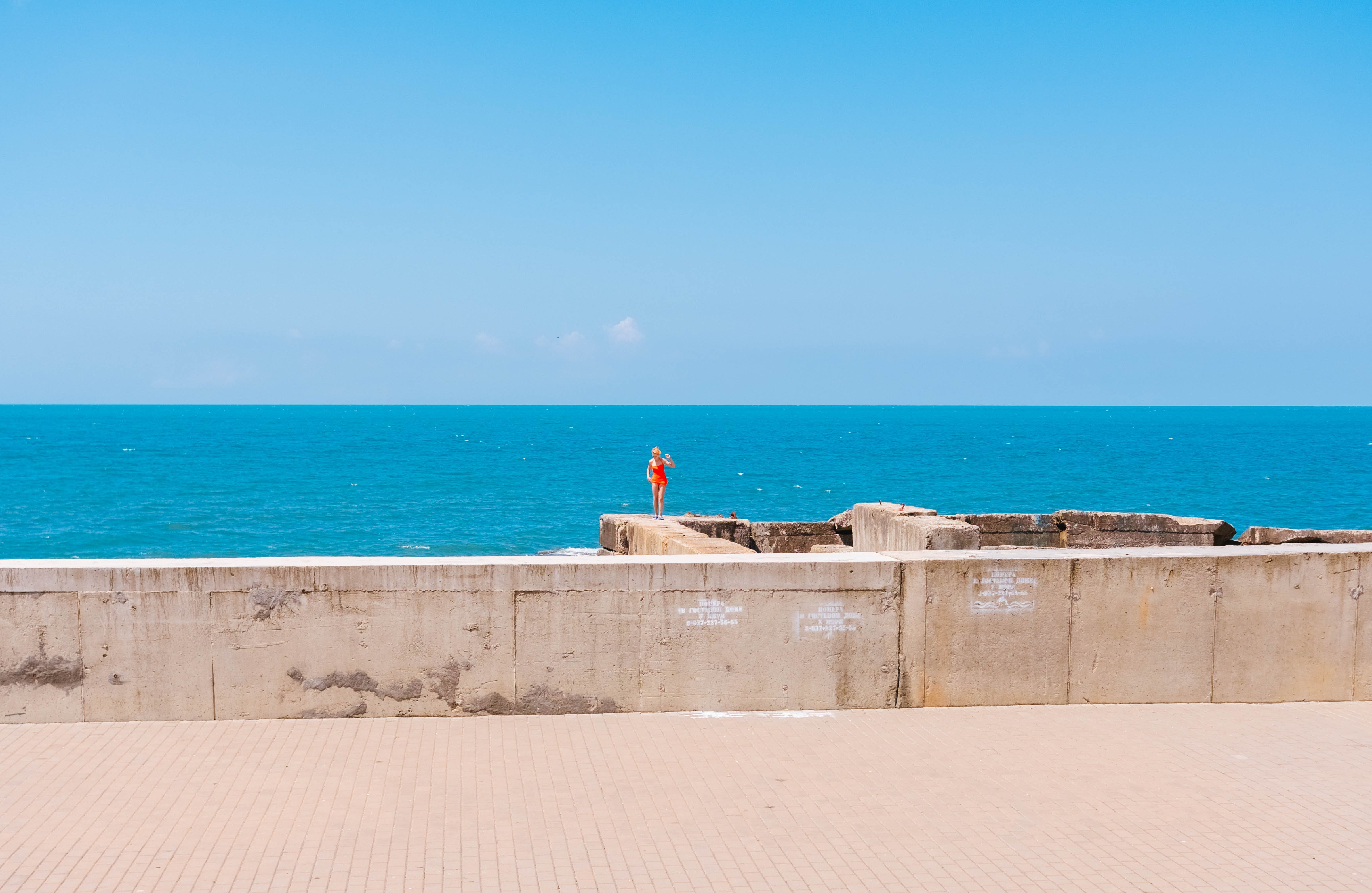 Person Standing On Concrete Wall Near Ocean Water Under Clear Blue Sky