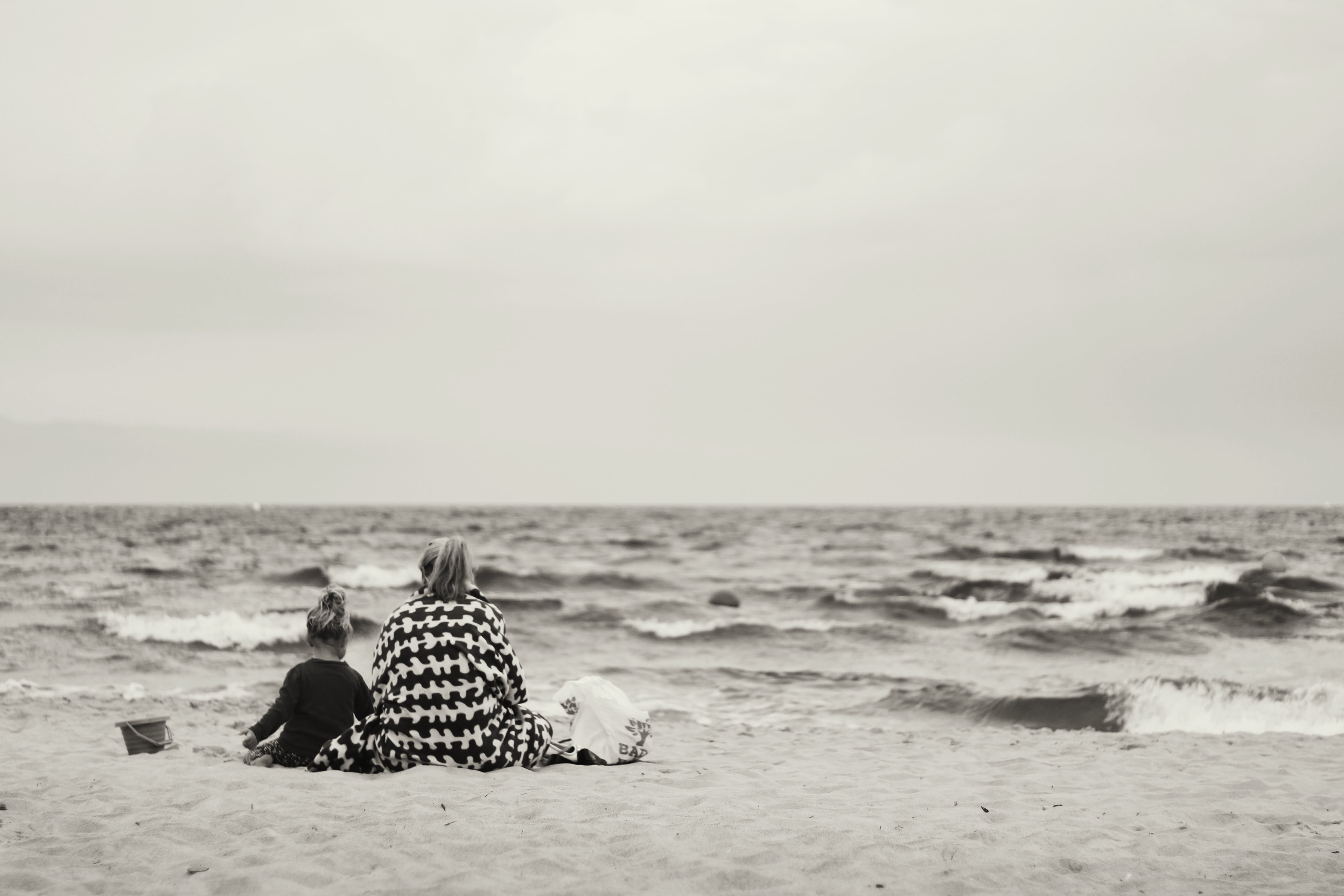 Woman And Child Sitting On Sand Near Body Of Water