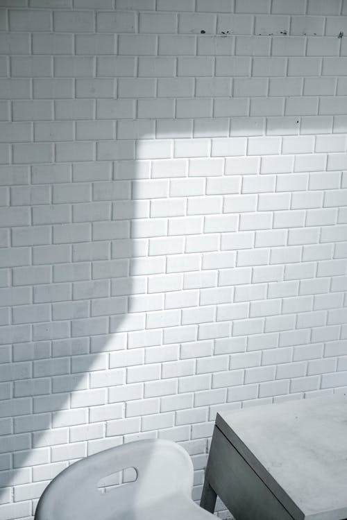 White Brick Wall Near White Chair