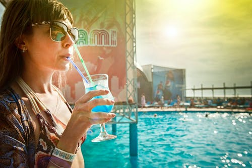 Woman Zipping Blue Drinks Beside In-ground Pool