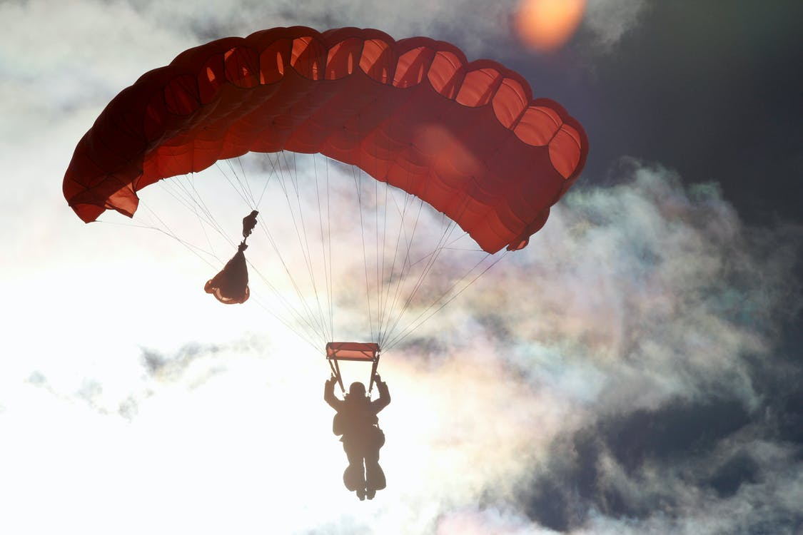 Person Riding on Red Parachute