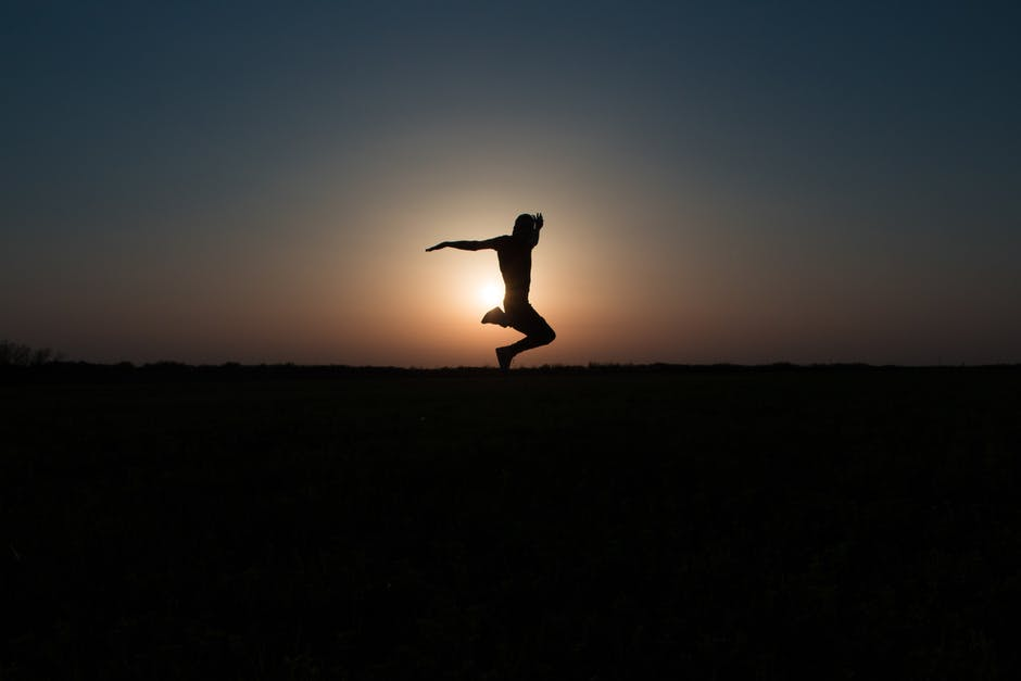 Silhouette Photo of Jumping Person during Twilight Hour