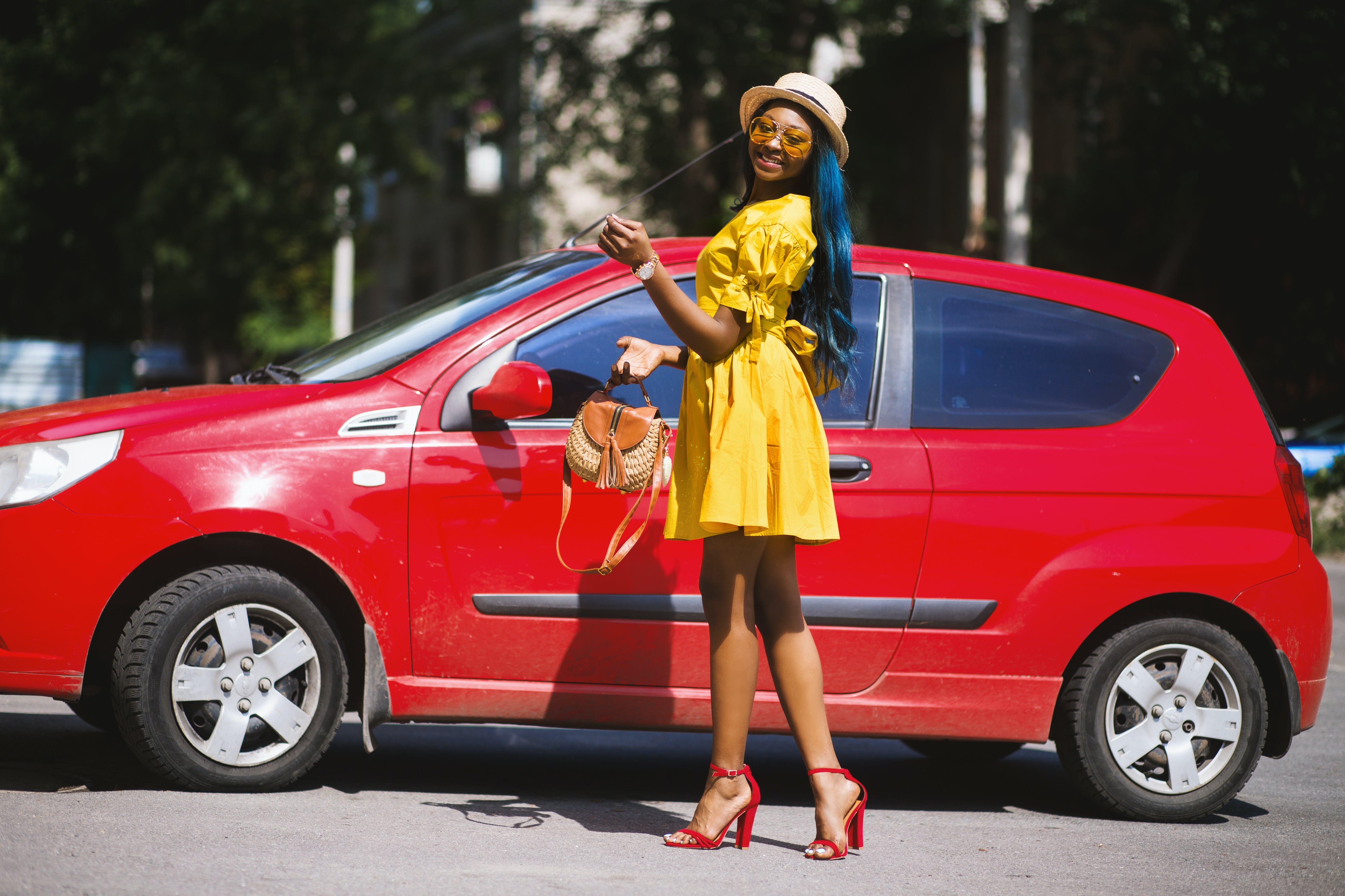 Woman Standing Beside Red 3-door Hatchback