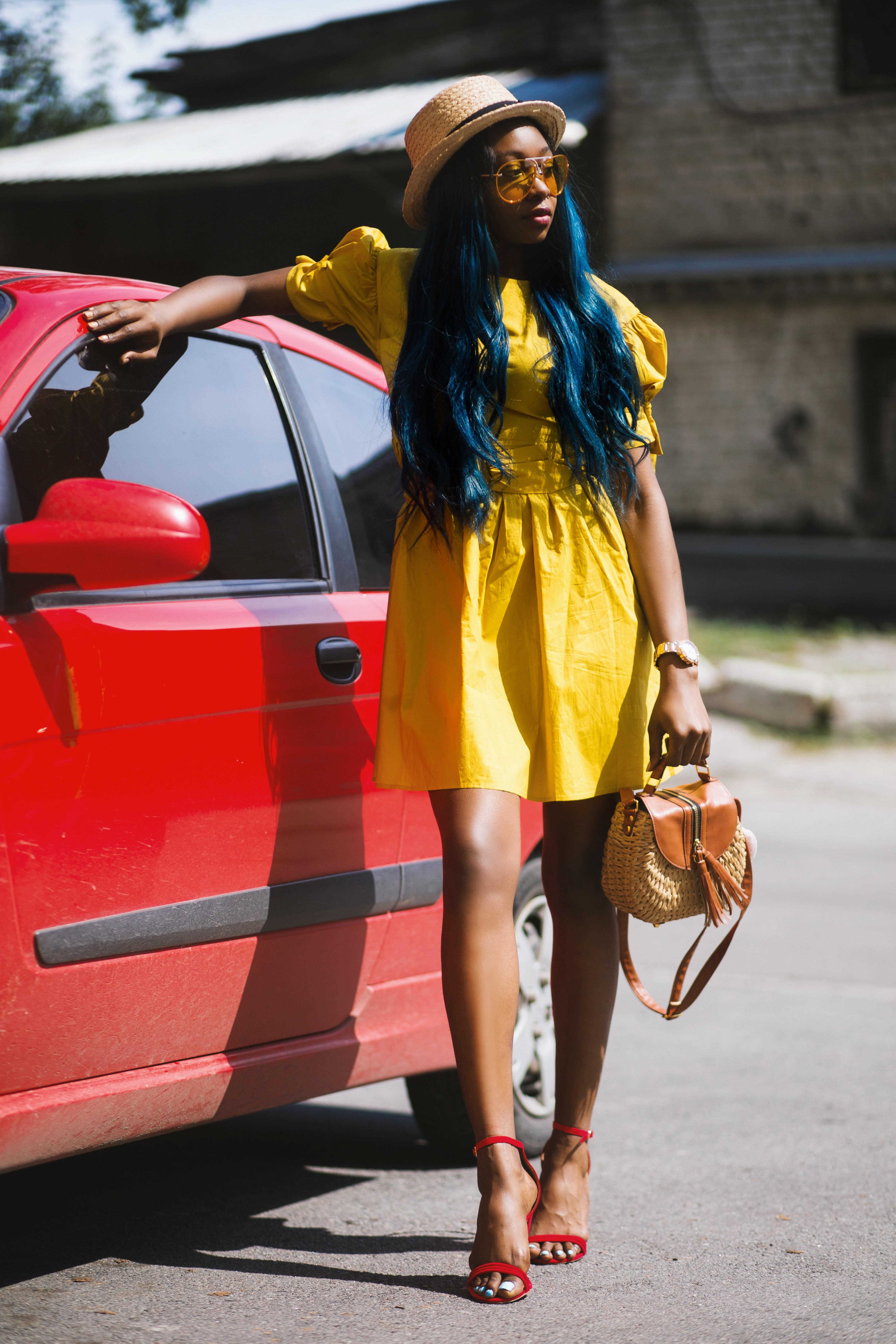 fa7c4cf2e2f Woman in Yellow Mini Dress Holding Handbag Beside Red Car. Godisable Jacob
