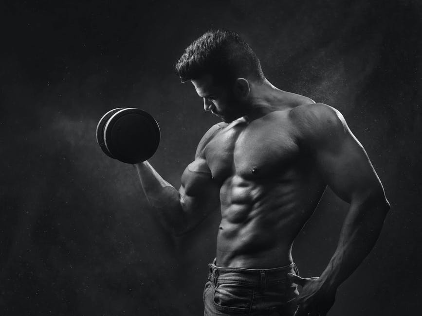 Man Holding Black Dumbbell