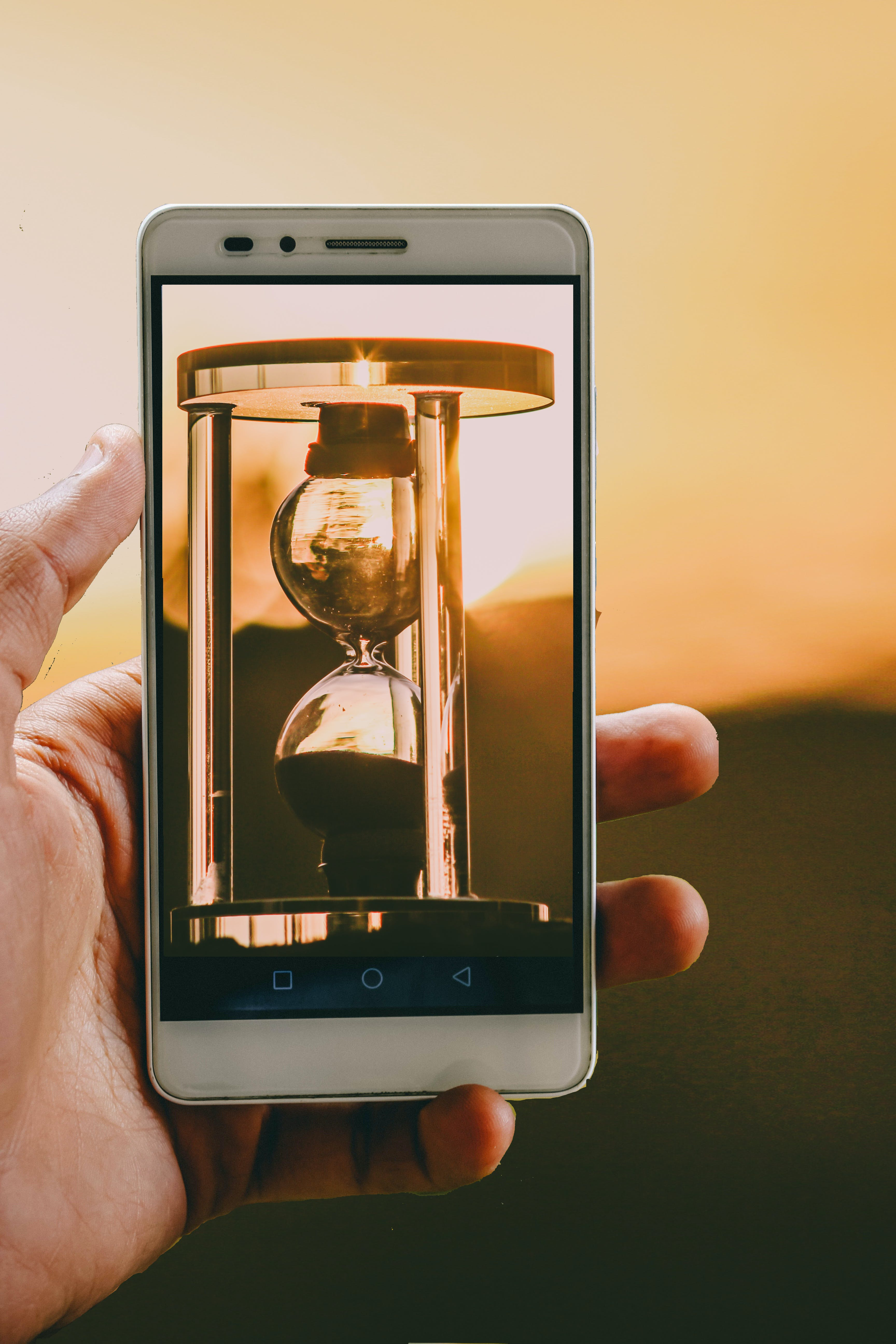 Person Holding Smartphone Showing Hour Glass