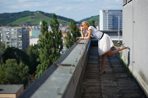 Woman Leaning on the Edge of a Building
