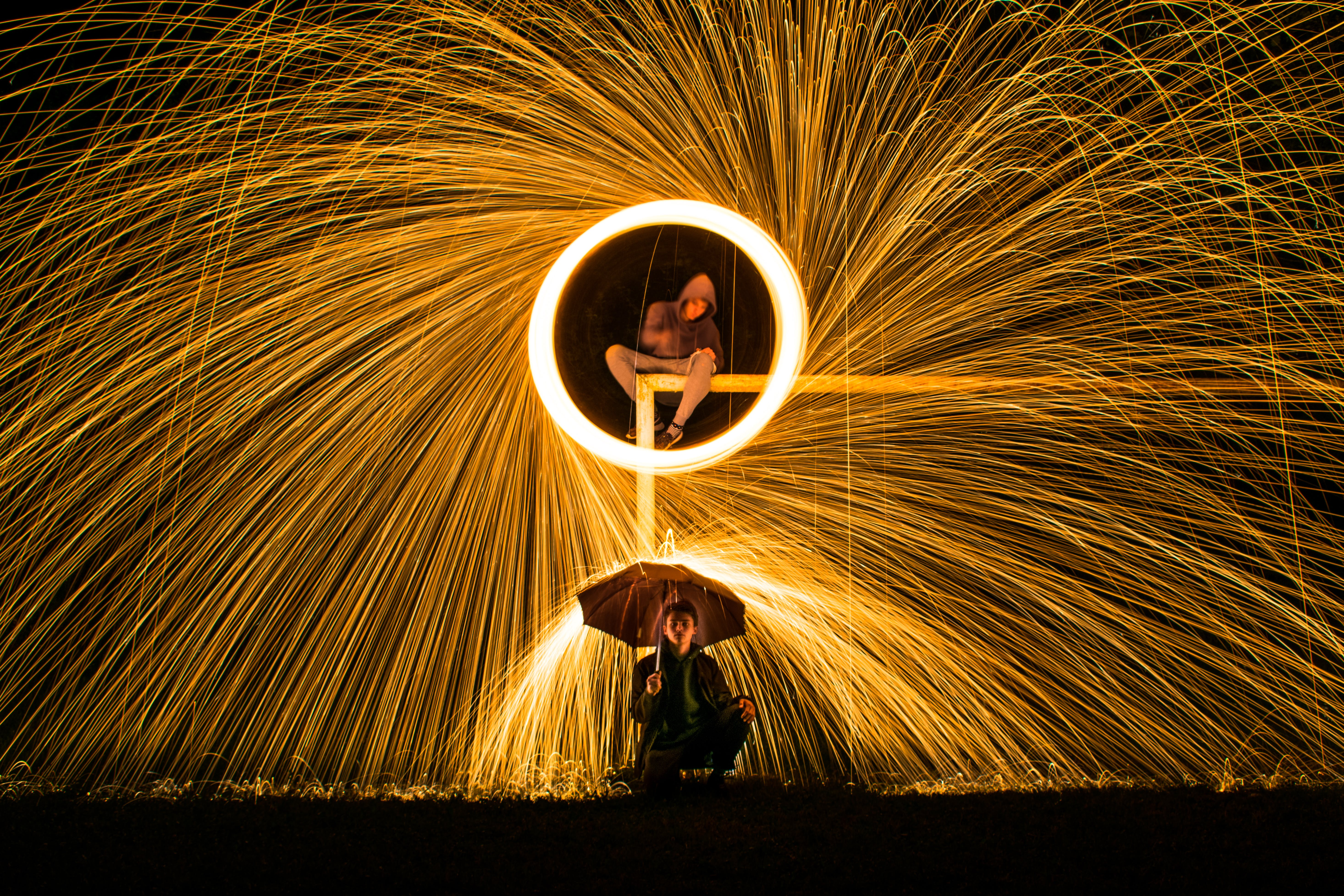 Time Lapse Photography of Person Making Firework Spark Under Person Holding Umbrella during Nighttime