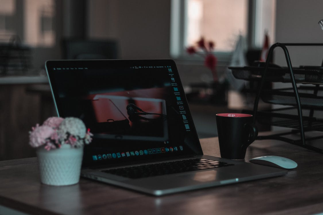 Macbook on Table Beside Mug in Shallow Focus Photography