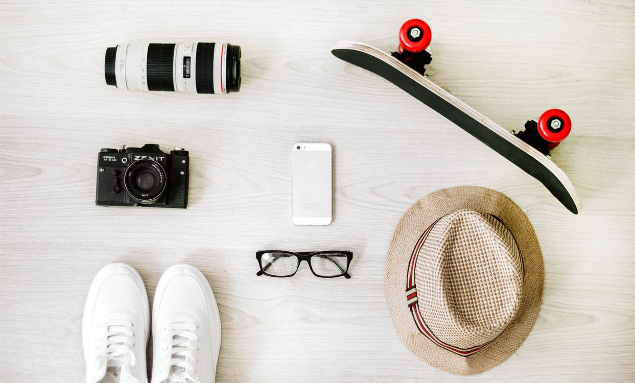 Photography of Black Skateboard, White Iphone 5, Brown Hat, Black Point-and-shoot Camera, and Zoom Lens