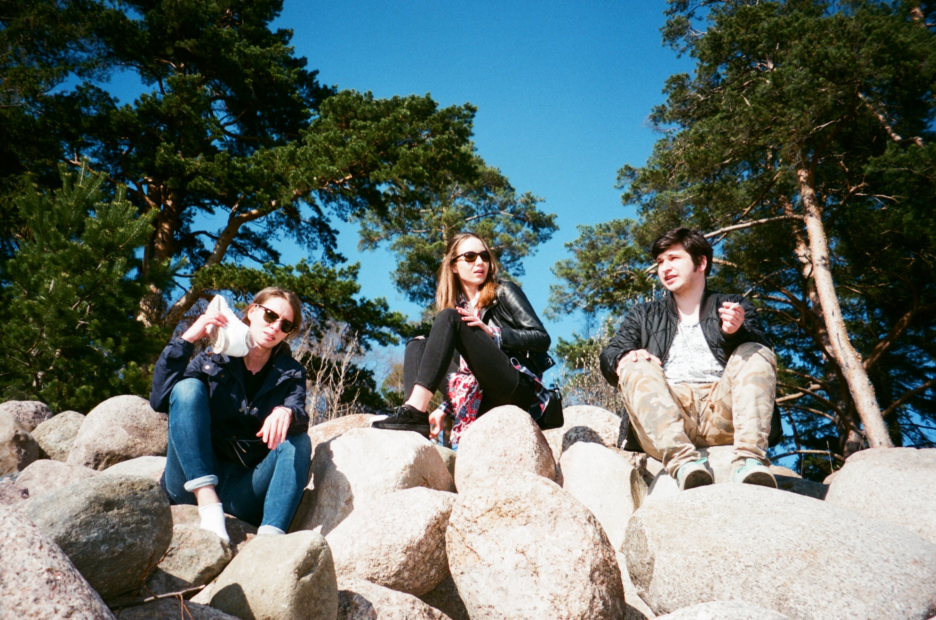 Three Person Sitting on Rock Formation