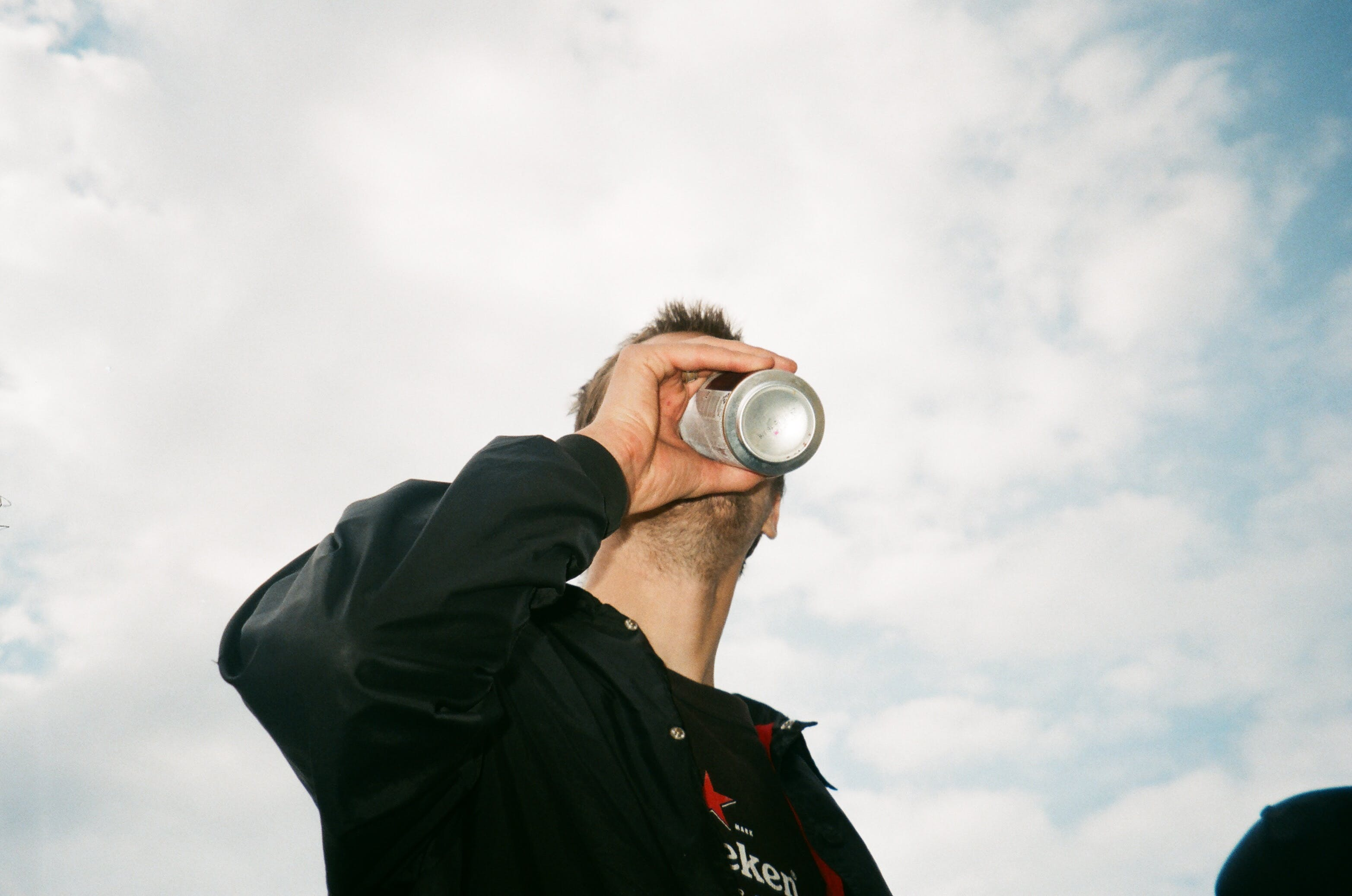 Low Angle Photography of Man Drinking Gray Labeled Can
