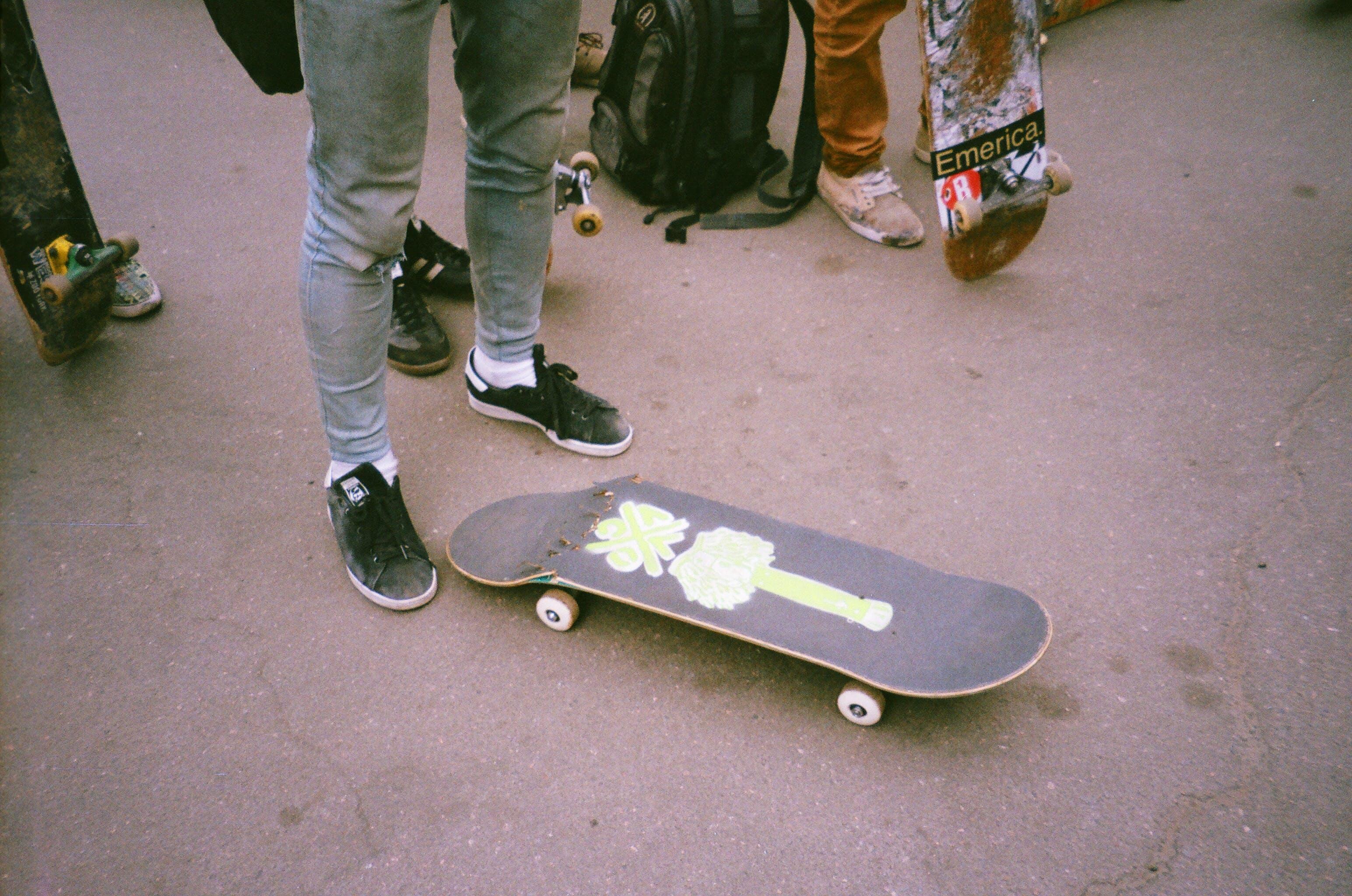 Person Standing Beside Broken Skateboard