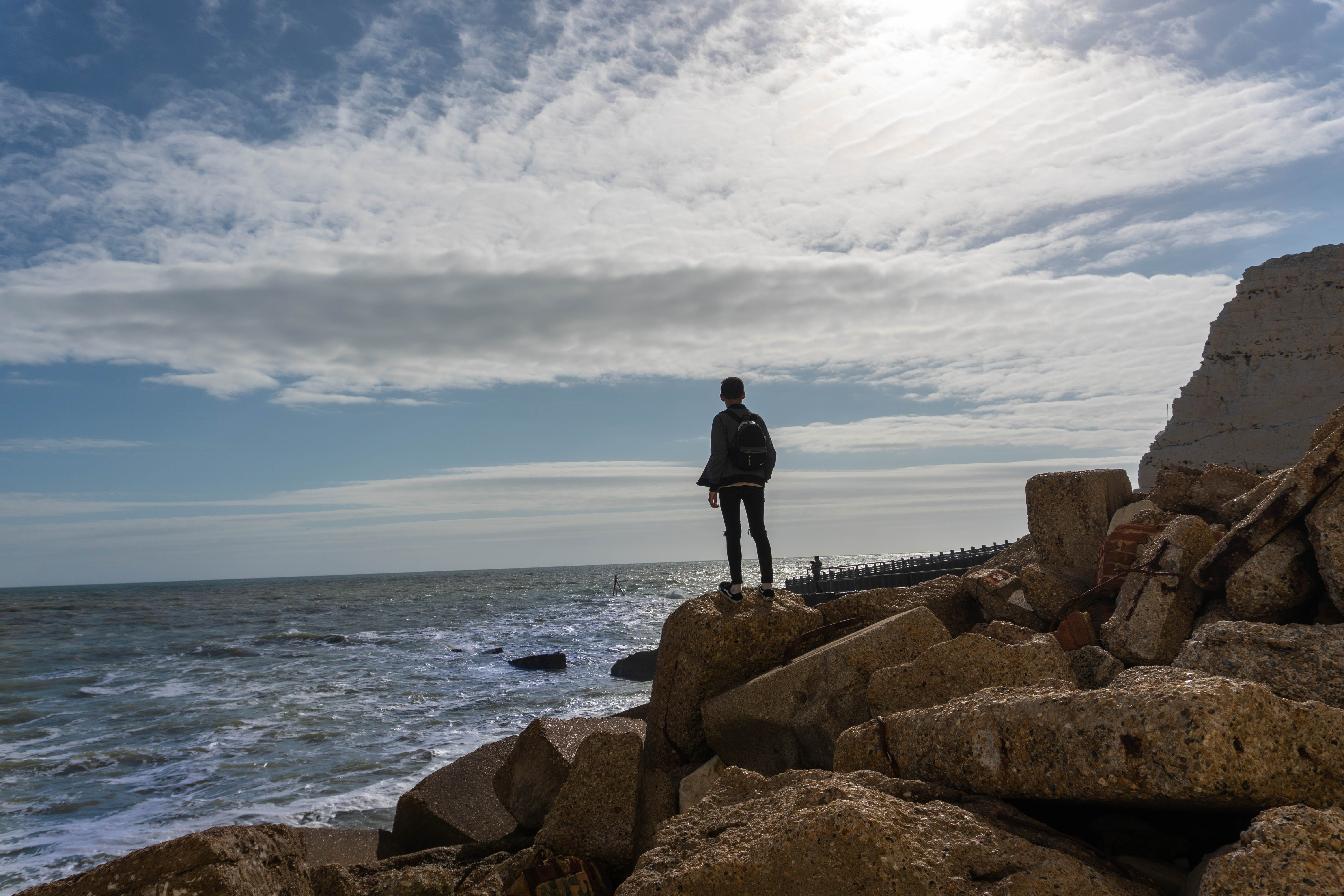 Person Standing on Rock in Front of Sea