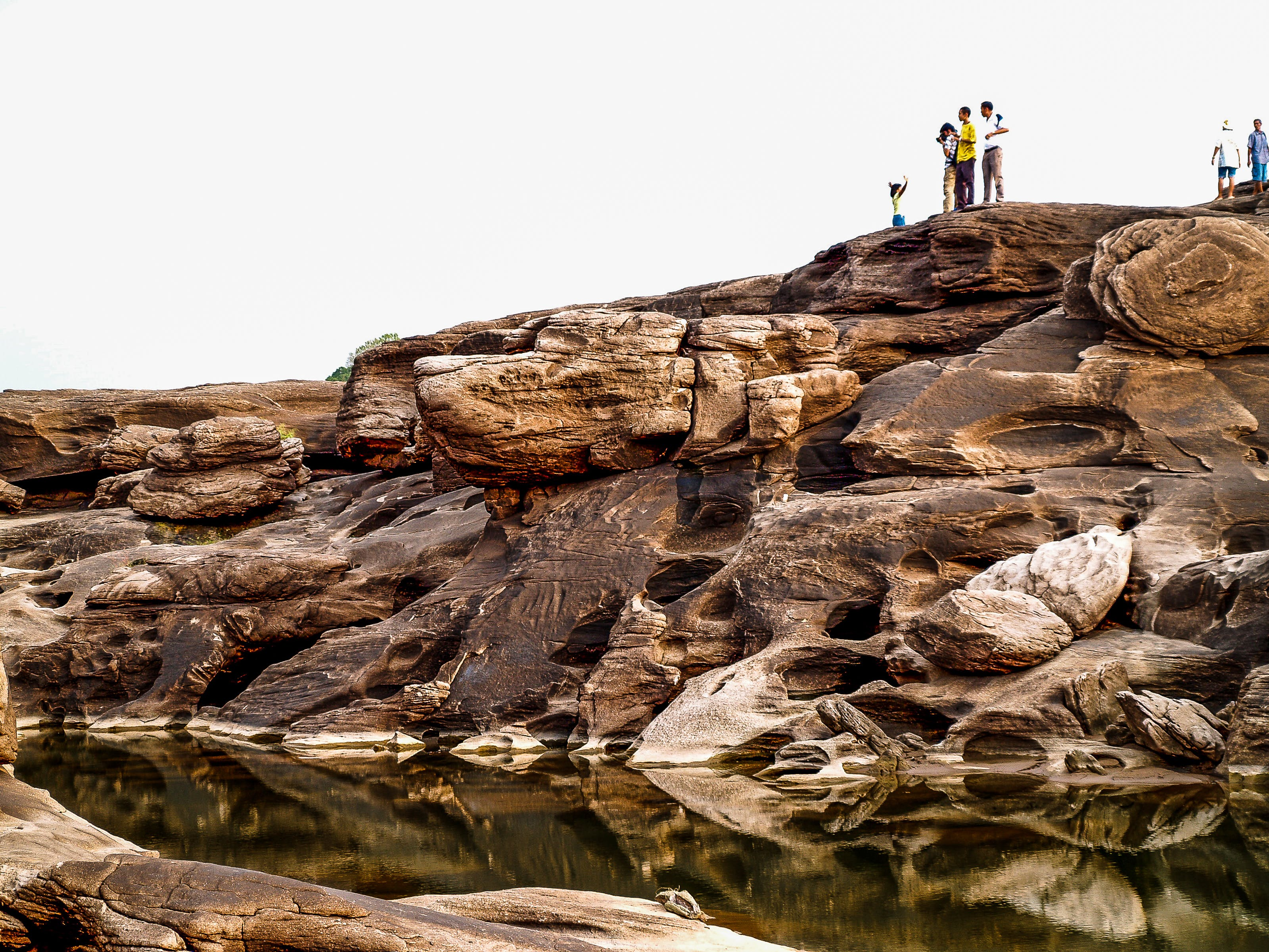 People Standing on Brown Cliff