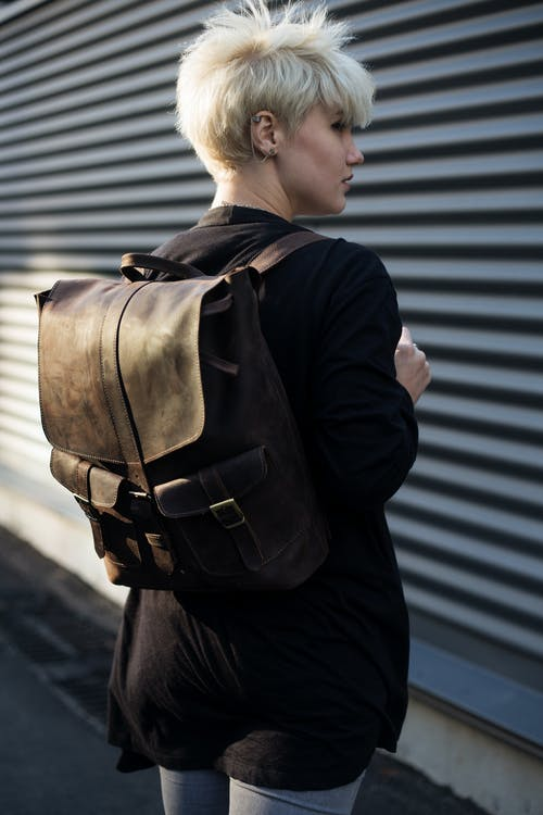 Woman Carrying Brown Leather Backpack Posing in Front of Roll-up Door at Daytime