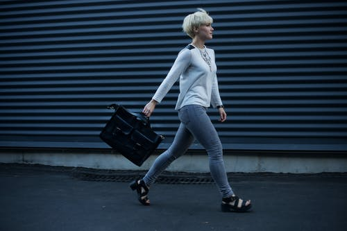 Woman Holding Black Leather Handbag Walking on The Street