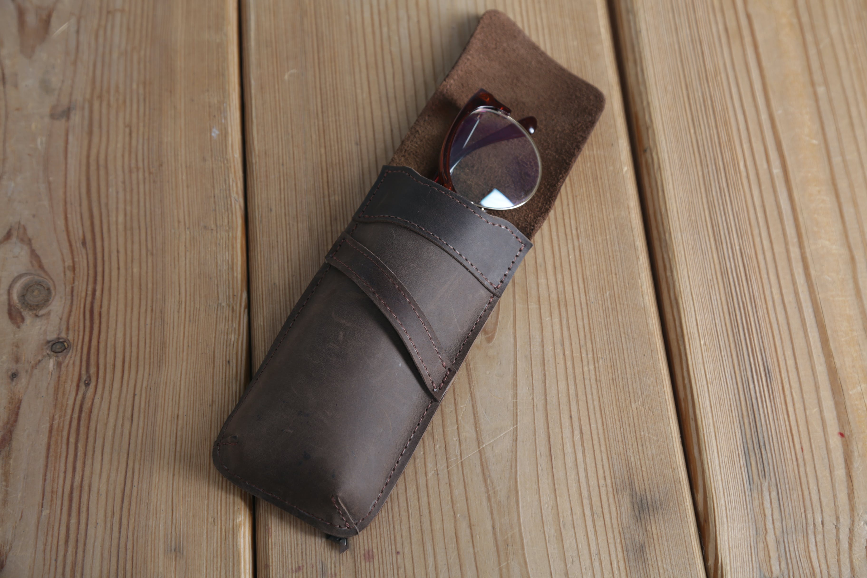 Eyeglasses in Brown Leather Case on Top of Wooden Surface