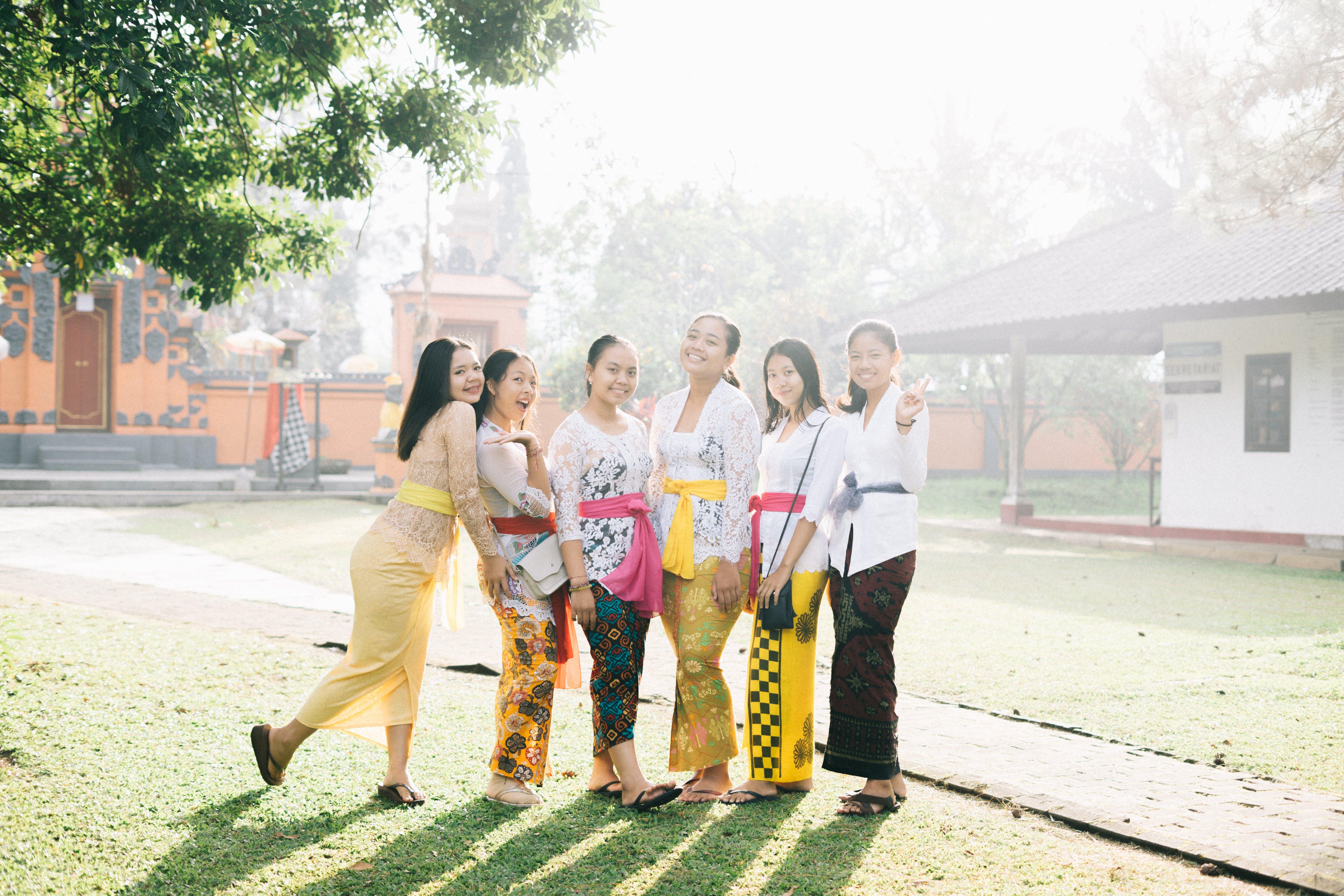 Six Women Standing Near Orange Building Taking Photo