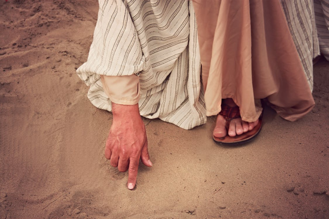 Person Touching Sand With Right Index Finger