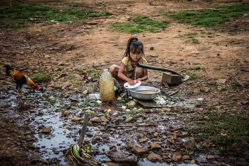 Girl Washing Dishes Outdoors Front of Hose