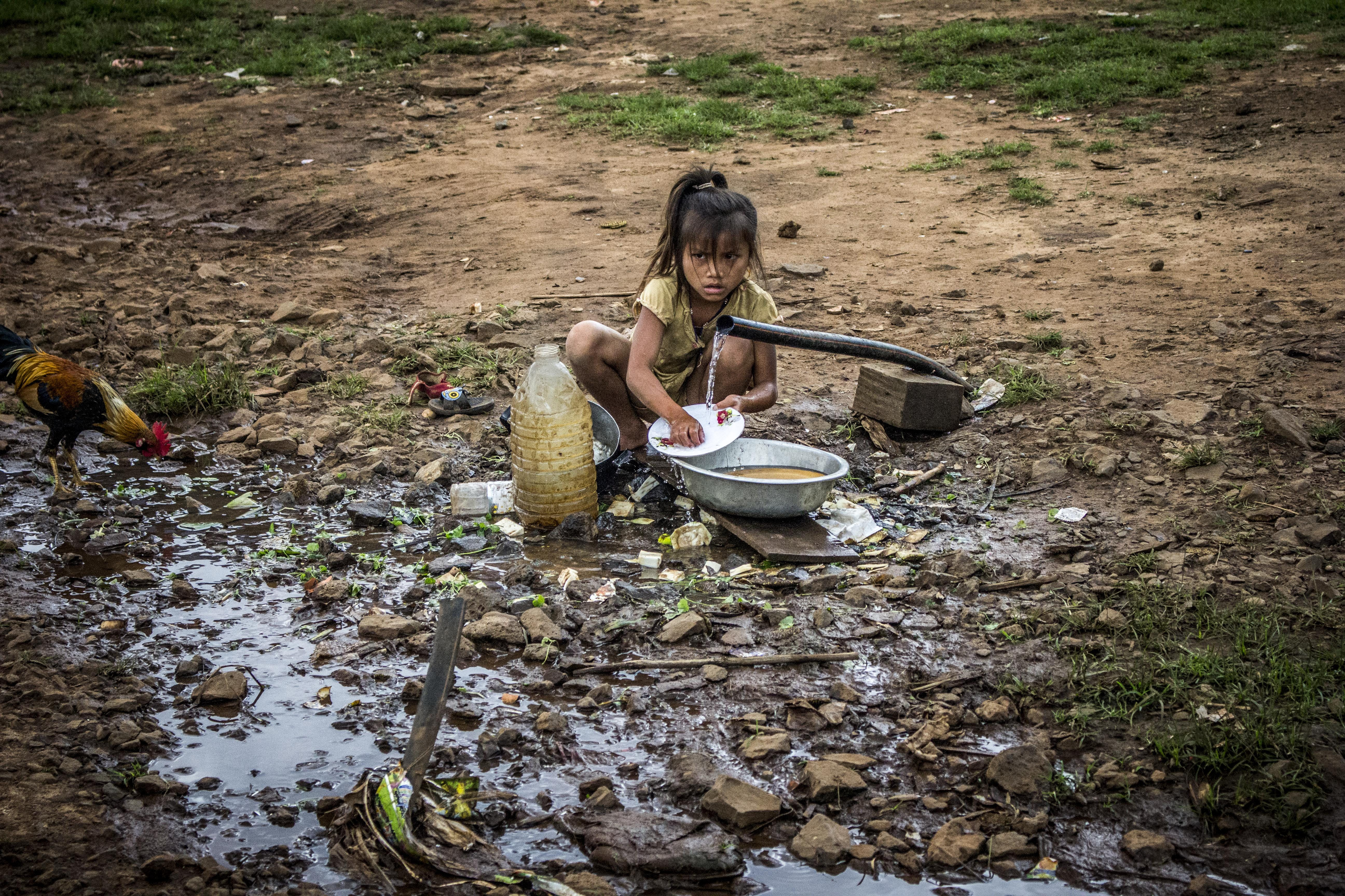 Girl Washing Dishes Sitting Near Plastic Bottle