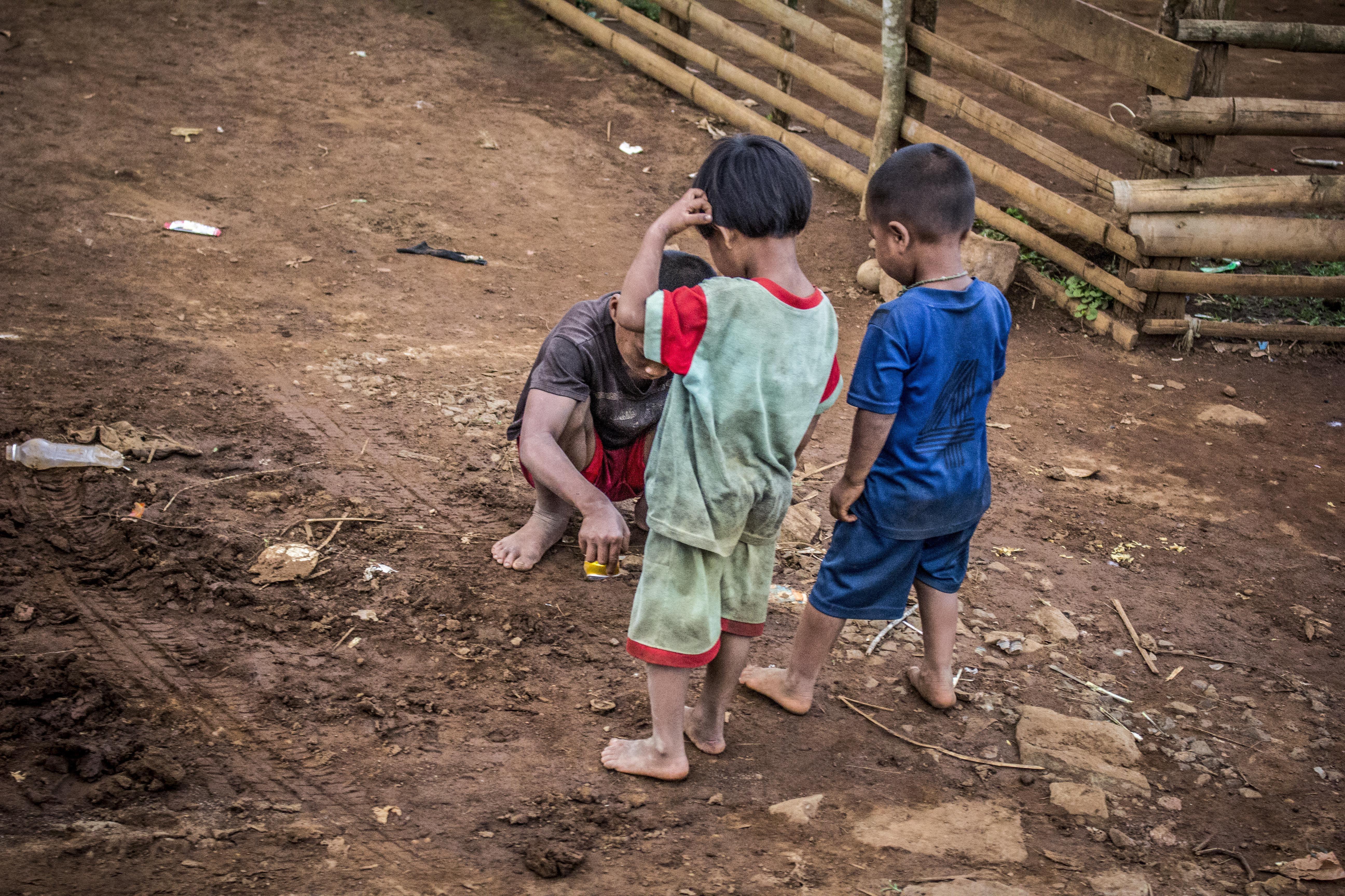 Three Children Standing on Brown Soil