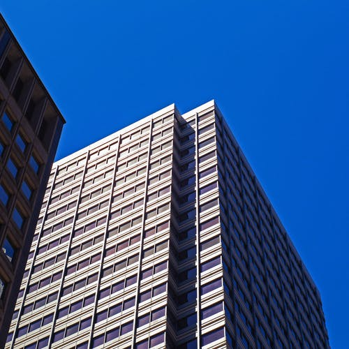 Low-angle Photo of White Concrete Building Under Blue Sky