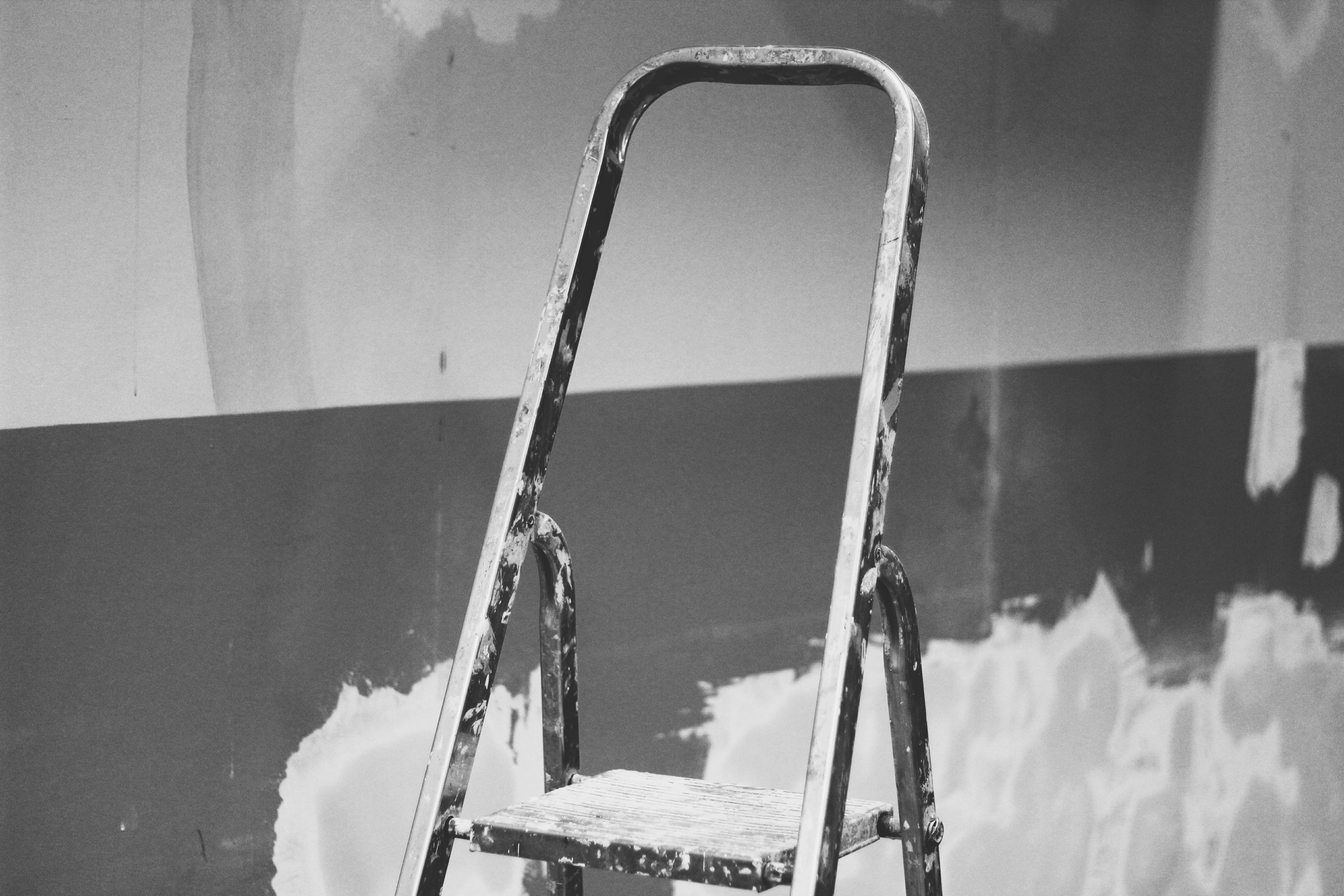 Black and Gray Step Ladder in Front of Wall
