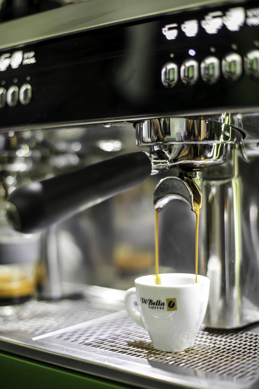 White Ceramic Di Bella Espresso Cup on Black and Gray Espresso Machine