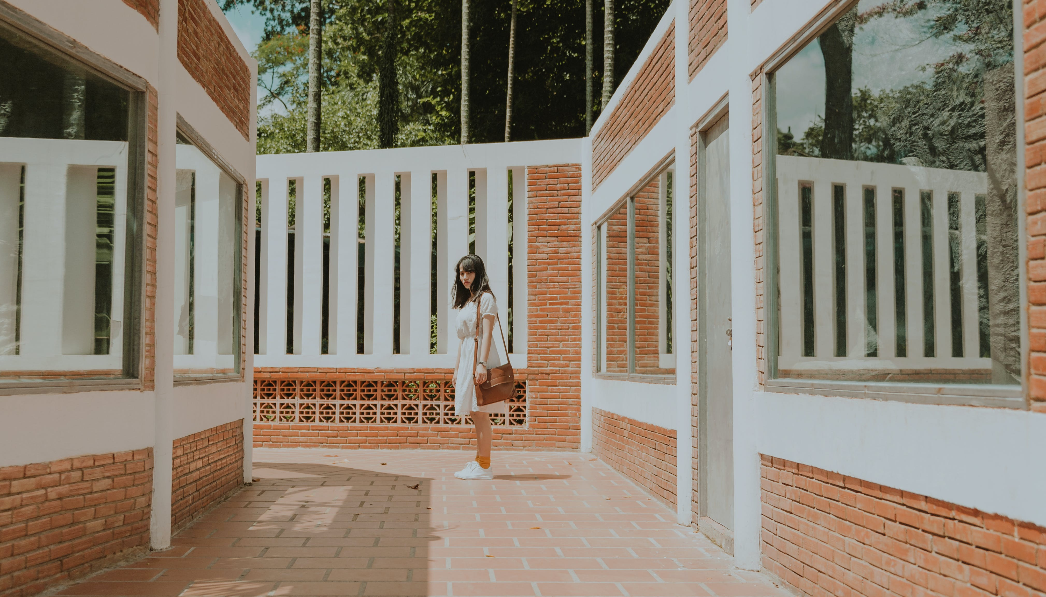 Woman Standing in the Middle of Brick Wall House