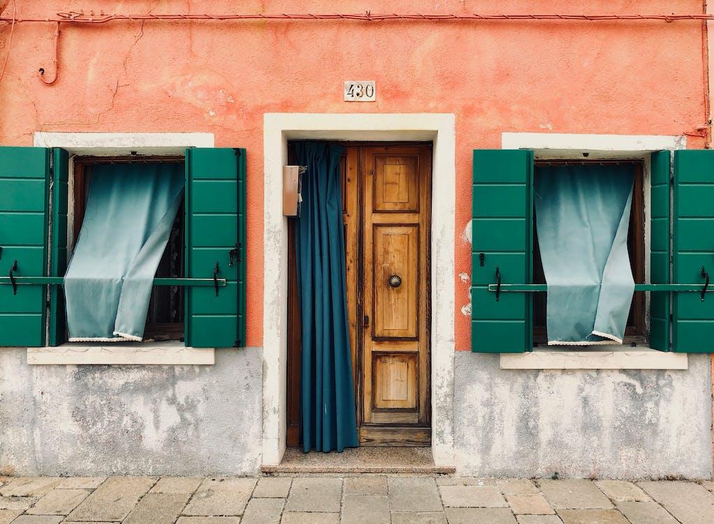 Brown Wooden Door Opened With Green Window Curtains