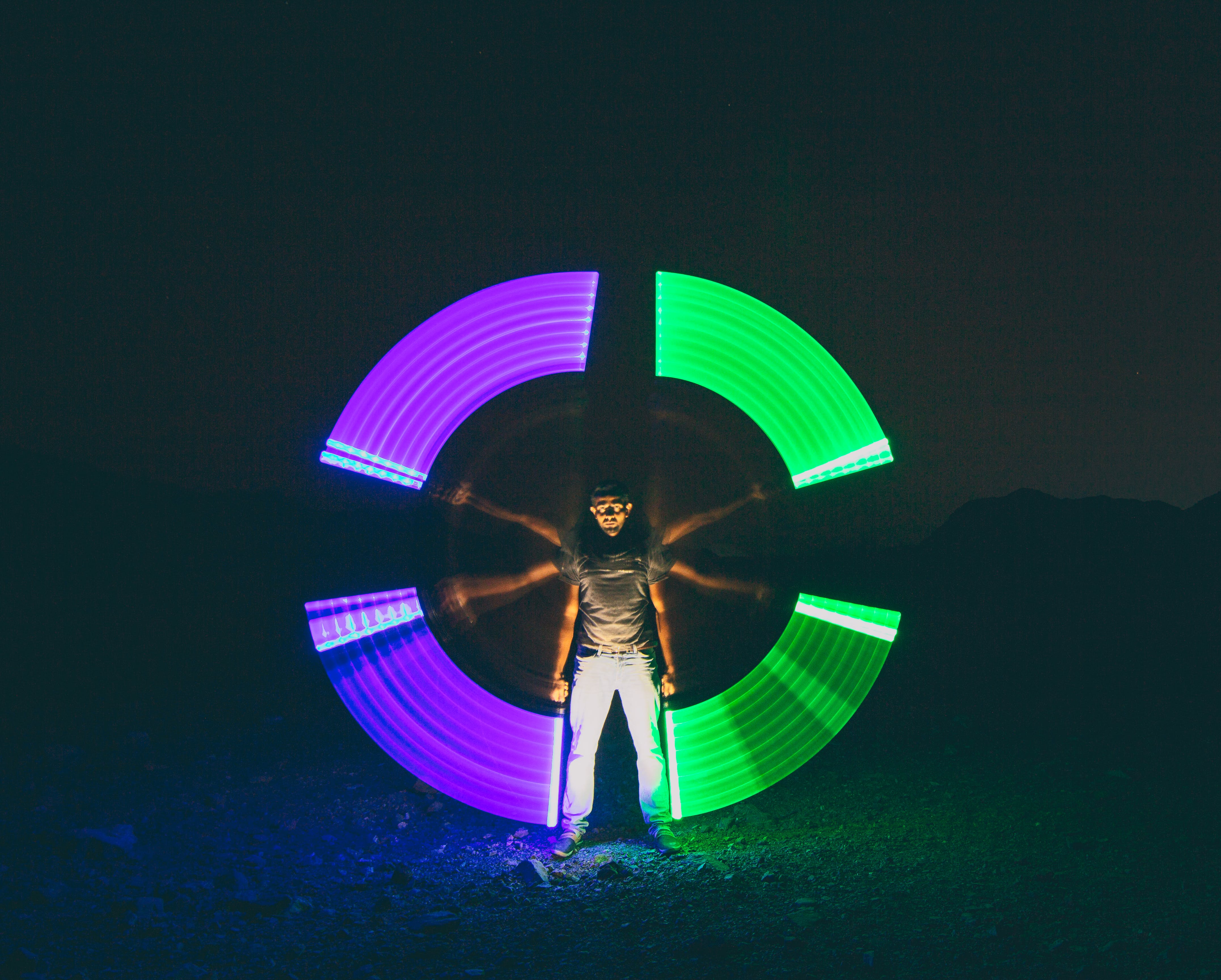 Time Lapse Photography of Man Holding Purple and Green Light Fixtures