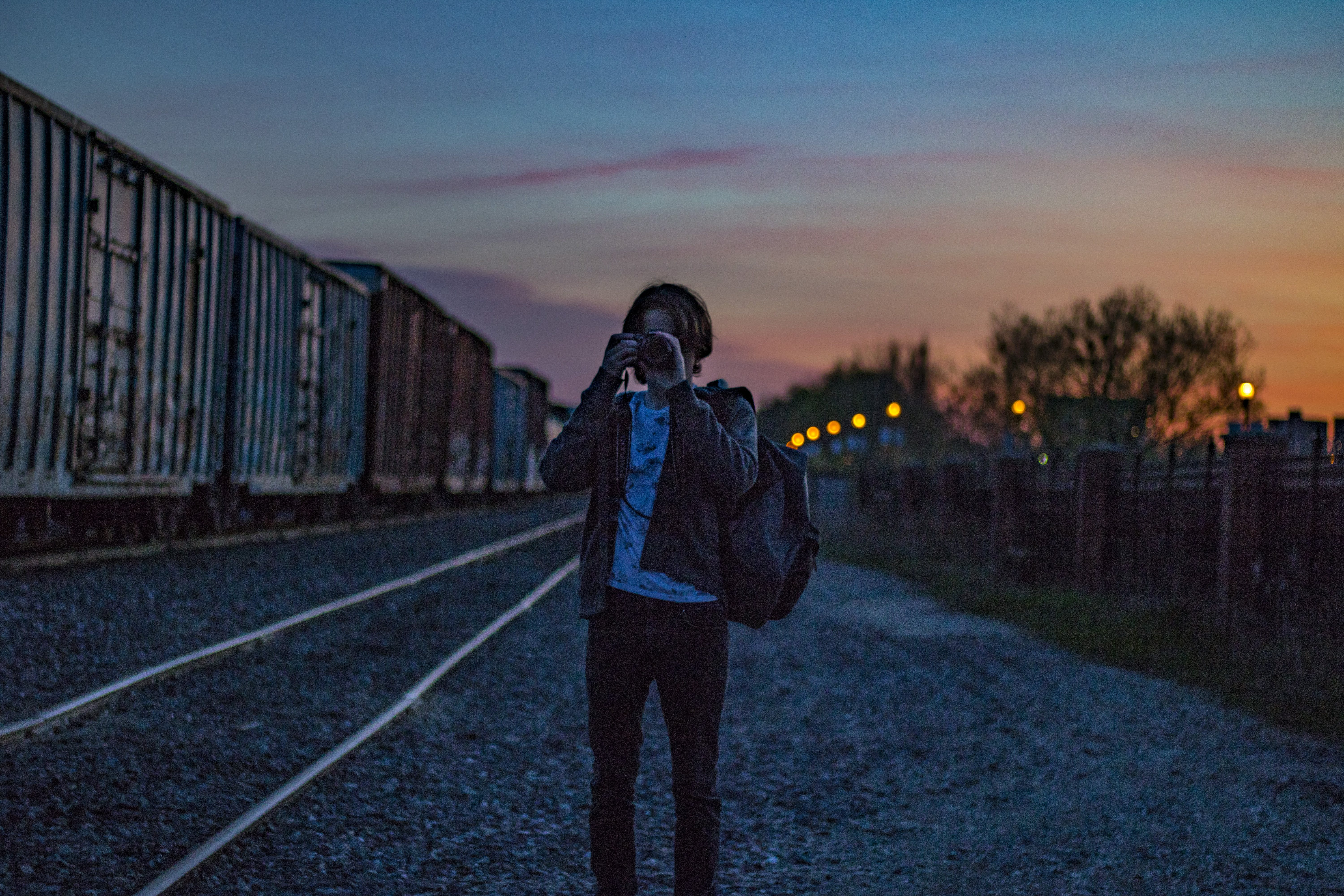 Man Wearing Brown Jacket With Backpack Taking Photo during Golden Hour