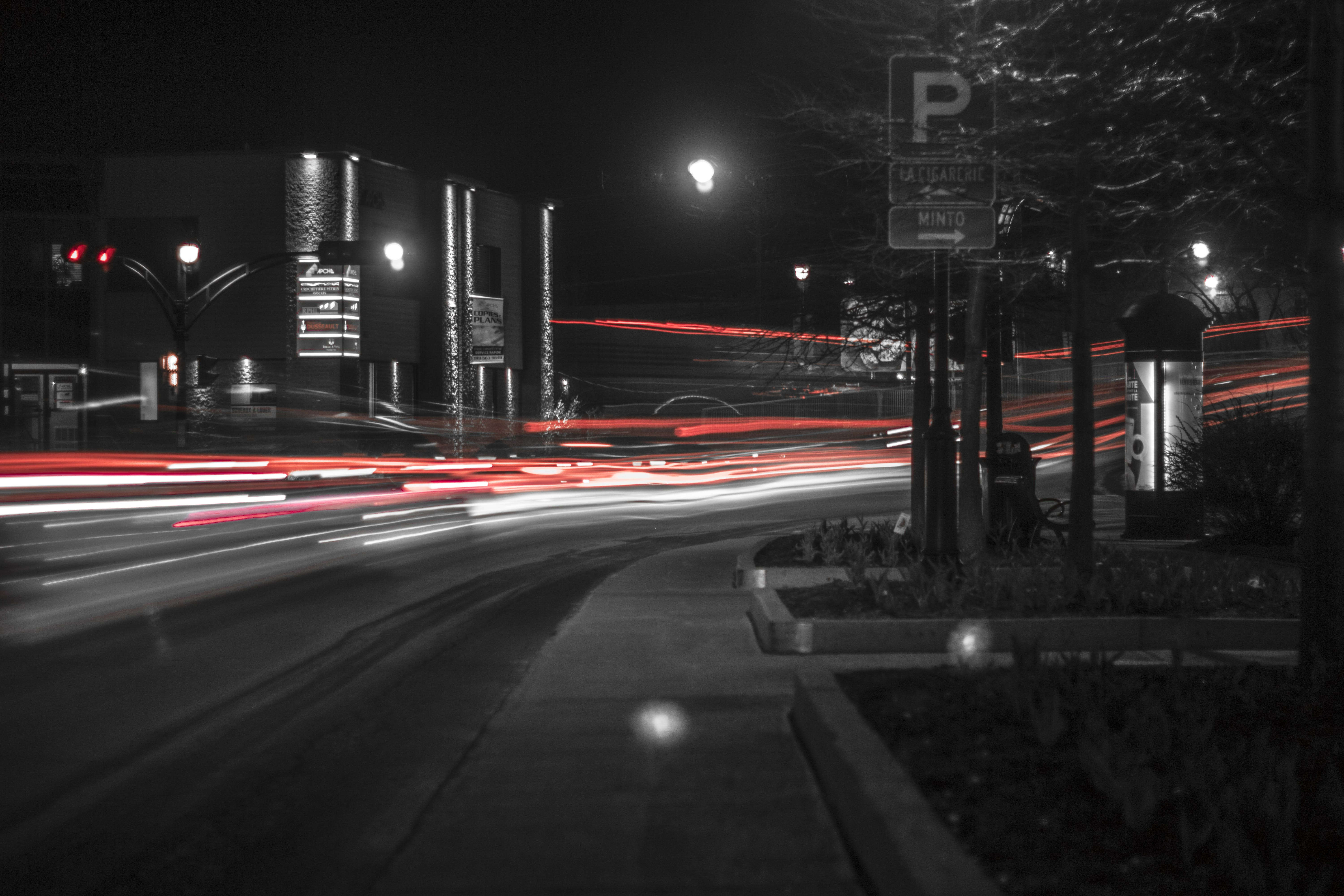 Grayscale and Time Lapse Photo of Vehicle at Night Time
