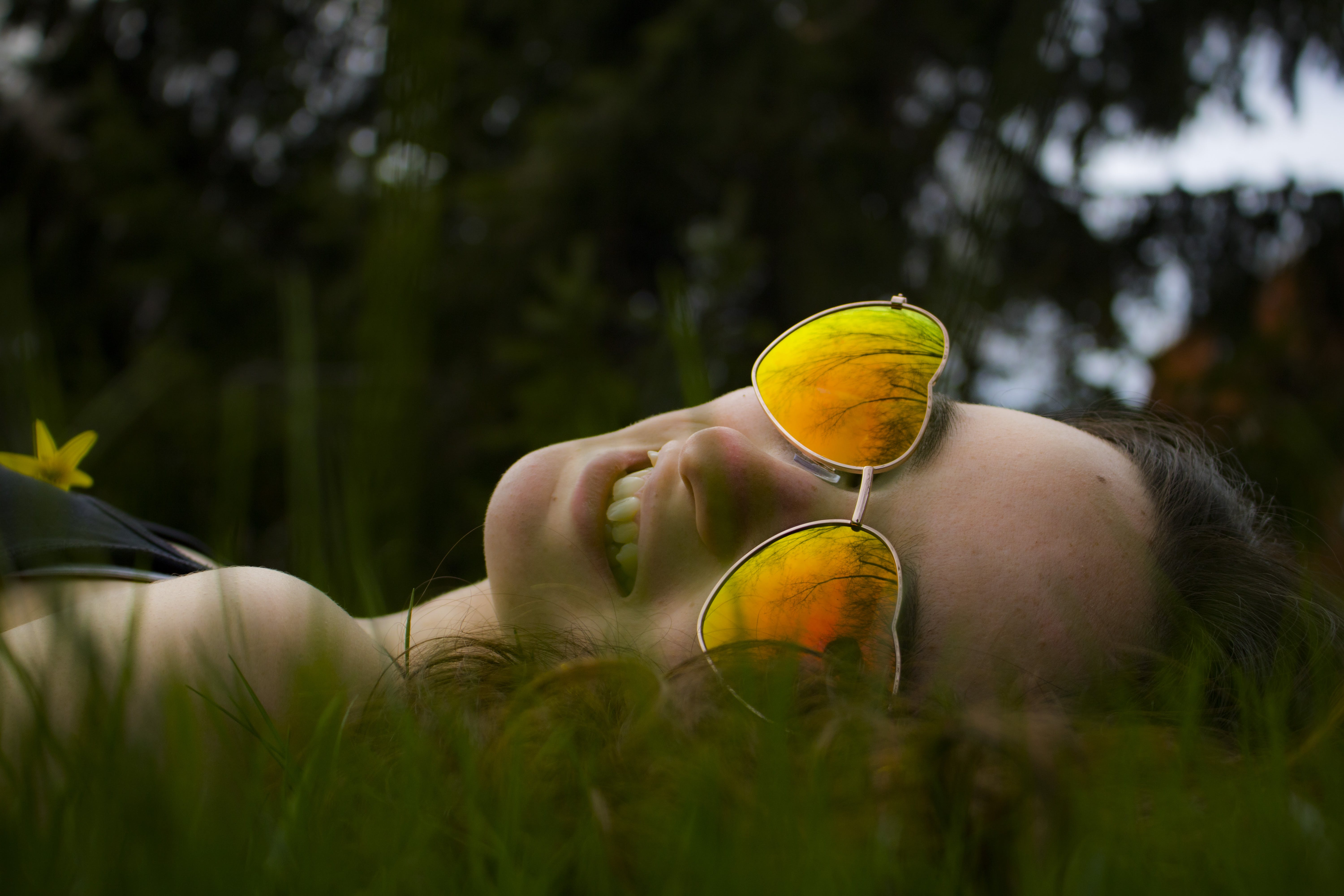 Lying Woman on Green Grasses With Gold-colored Sunglasses Closeup Photo