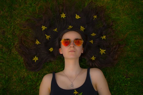 Photo of Lying Woman on Green Grass Wearing Red Lens Heart Sunglasses With Yellow Petal Flowers on Hair