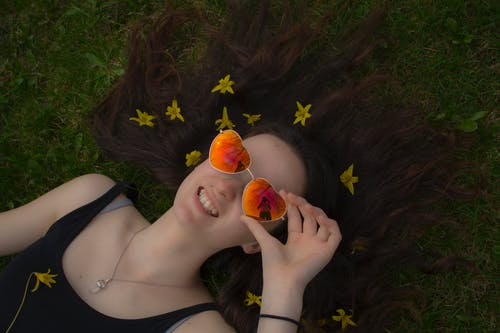 Woman Holding Her Orange Sunglasses While Laying Down on Grass