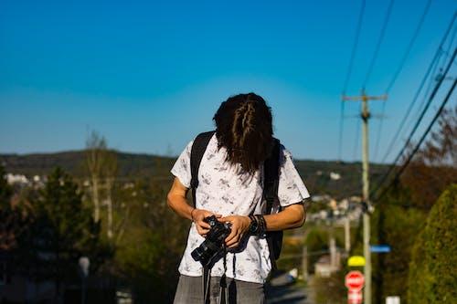 Man in White Floral Shirt Wearing Black Backpack Holding Black Dslr Camera Beside Green Plants Under Blue Skies