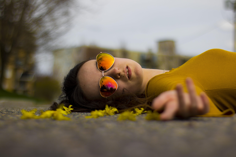 Closeup Photo of Woman Lying on Gray Pavement