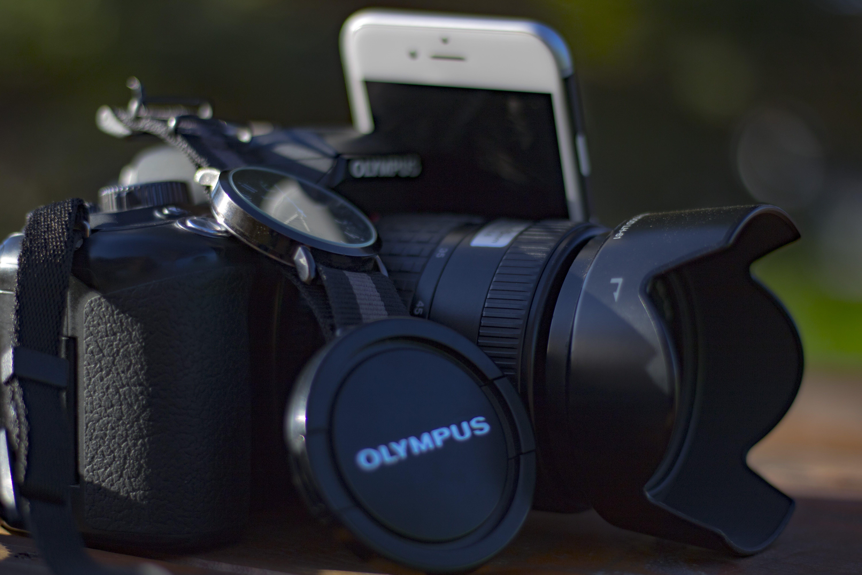 Black Olympus Dslr Camera Beside Silver Iphone 6