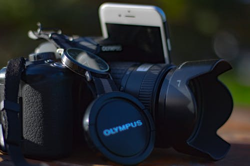 Black Olympus Dslr Camera Beside Silver Iphone 6
