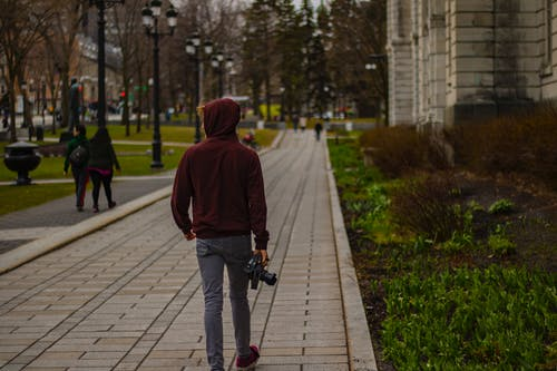Man Wearing Hoodie Walking on Concrete Pathway Holding Dslr Camera Near Concrete Building