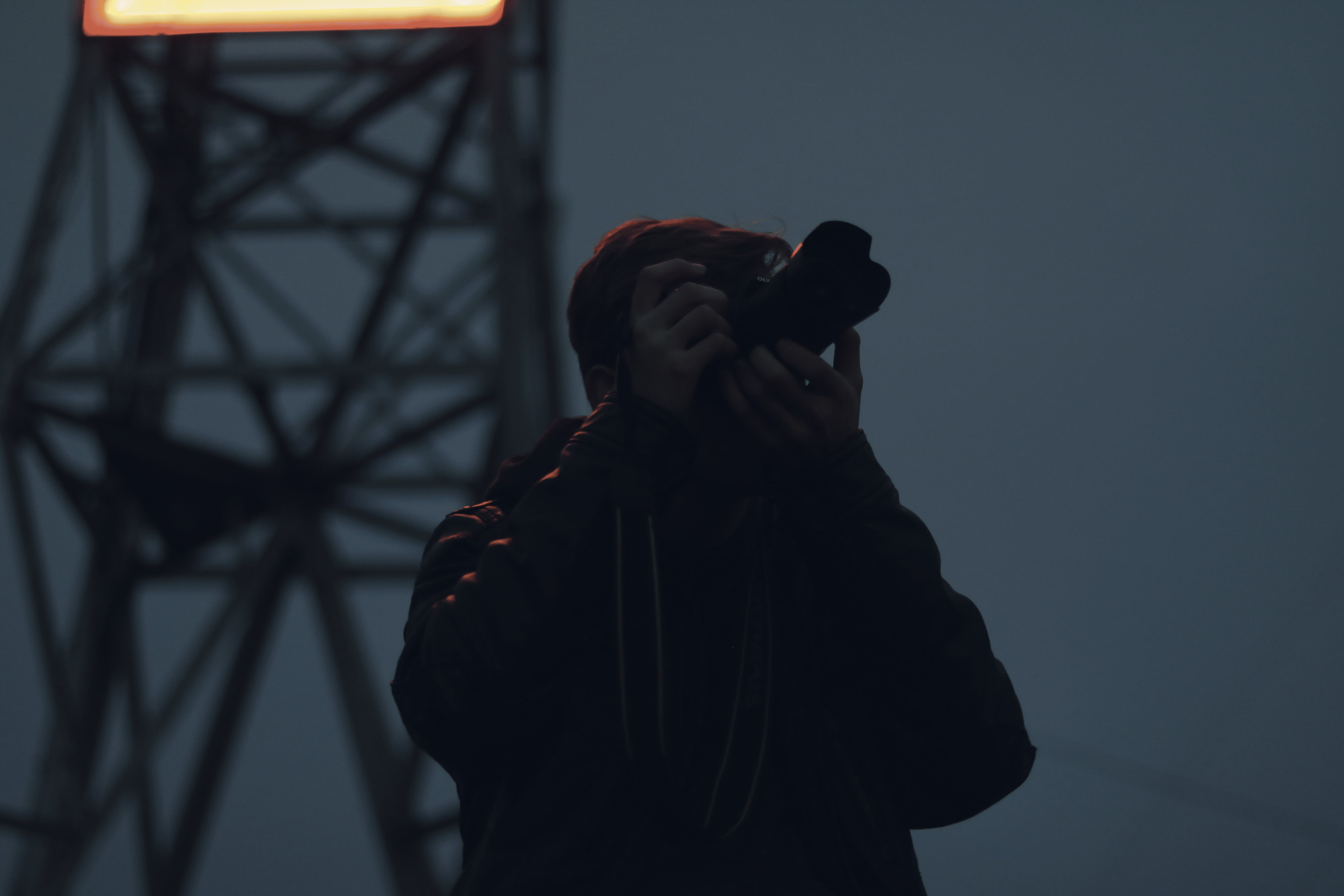 Silhouette Photography of Man Holding Dslr Camera