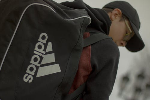 Shallow Focus Photography of Man in Black Hoodie Carrying Black Adidas Duffel Bag