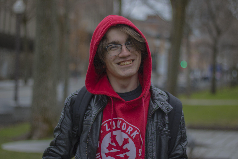 Smiling Man Wearing Black Zip-up Hoodie Near Trees