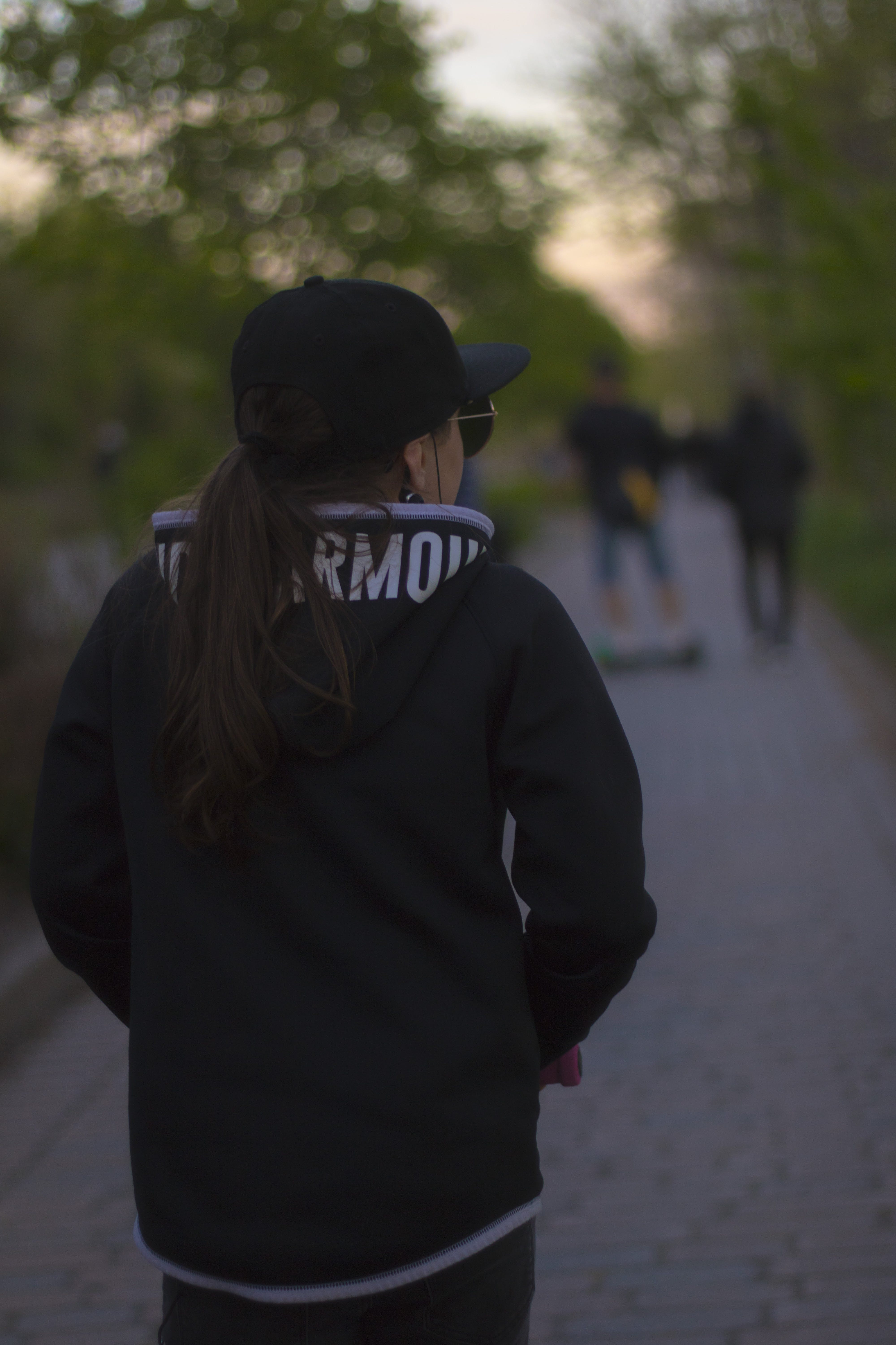 Shallow Depth of Field Photography of Person Walking Between Trees in Distant of Two People
